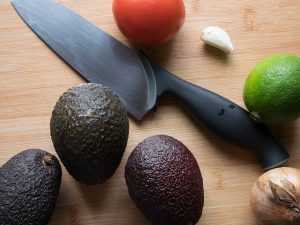 health benefits of potassium -- photo of avocados and tomato with kitchen knife on cutting board