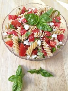 healthy pasta recipe -- pasta, tomatoes, and basil in glass bowl