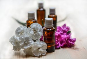 how to use essential oils -- photo of oils in brown bottles with fresh flowers