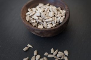 health benefits of sunflower seeds -- bowl of shelled seeds on dark counter