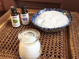 DIY bath salts -- photo of salts in bowl and bottles essential oils