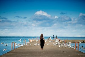 get outside photo of woman walking on dock by ocean
