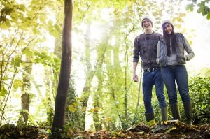 get outside photo of man and woman standing in forest