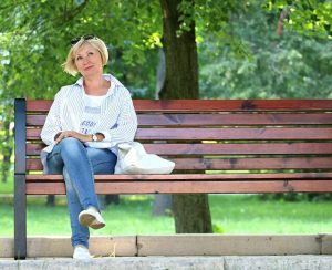get outside photo of woman seated on park bench by tree