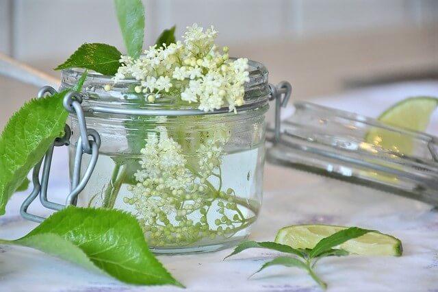 photo of elderflower blossoms in glass jar