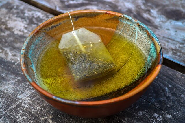 photo of green tea bag brewing in bowl