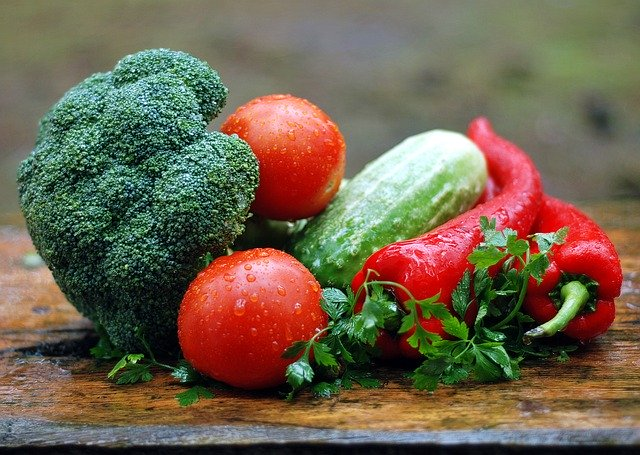 photo of vegetables to choose when eating seasonally: broccoli, tomatoes, cucumber, and peppers