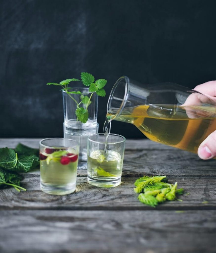 photo of spruce tip liqueur pouring from carafe into glass